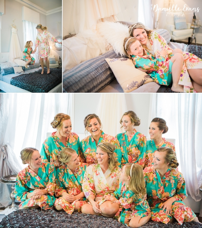 Bride in white floral robe jump on the bed with her flowergirl and laughing with bridal party in sea foam robes