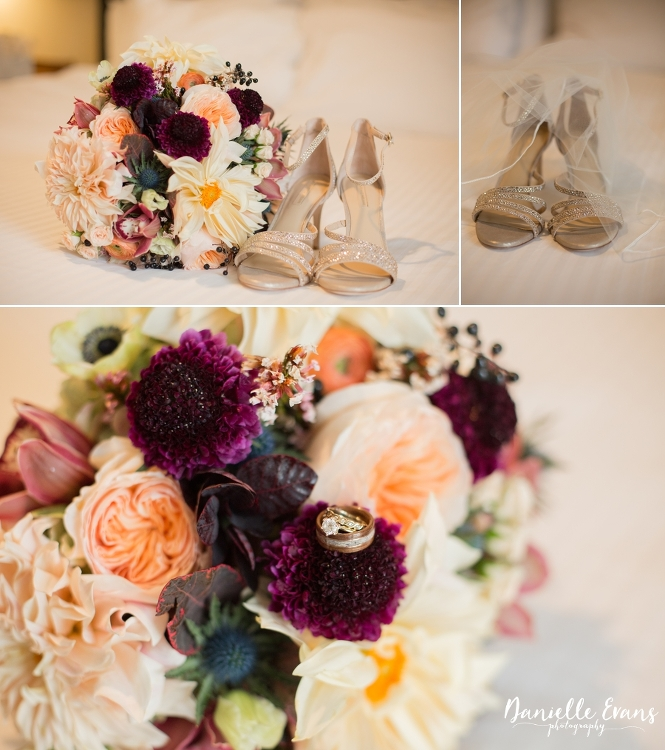 detail shot of bridal bouquet of peach, blush and eggplant flowers with wedding rings and wedding shoes
